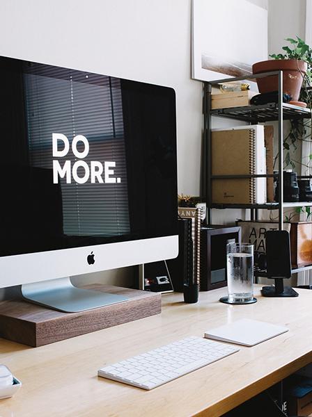 """Bureau avec ordinateur dont le fond d'écran indique la citation """"Do more"""". Représente l'activité de consultante en organisation, communication et gestion de Fabienne Bister"""